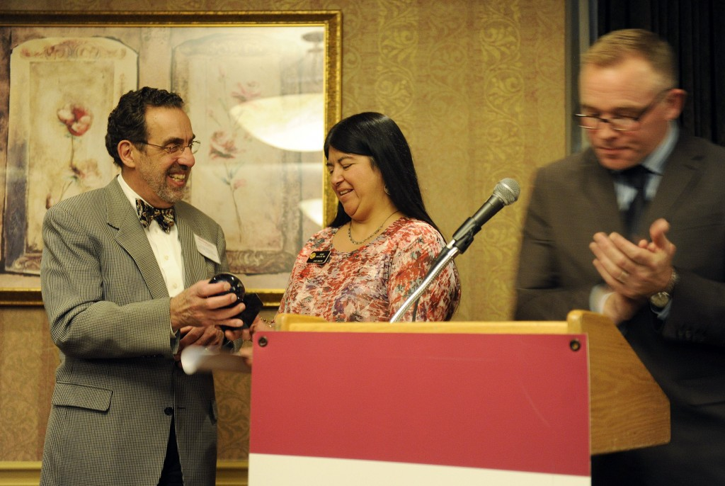 Dr. Paul Melinkovich of Denver Health presents an award to Sen. Irene Aguilar. Donald Moore, CEO of the Pueblo Community Health Center is at right.